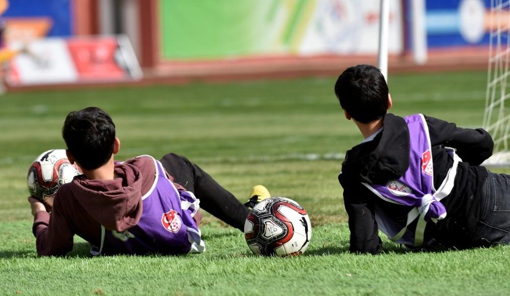 Top toplayıcı gençler maç sırasında plajda güneşlenir gibi güneşlendi